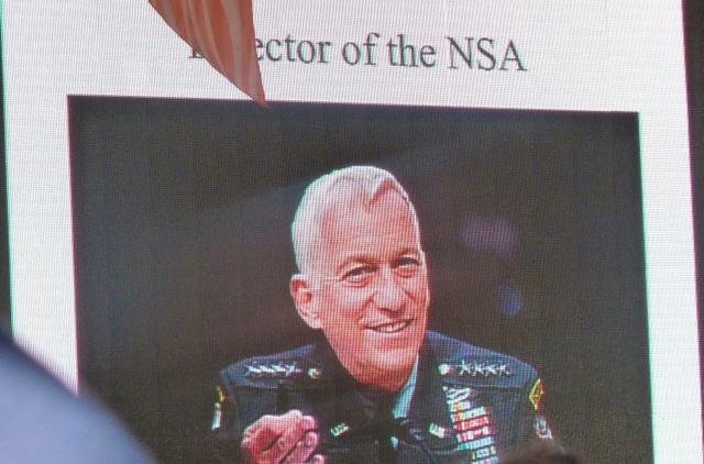 "A slide presented by David Bradley of The Atlantic featured a spoof photo of Walter Isaacson as ""Director of the NSA."""