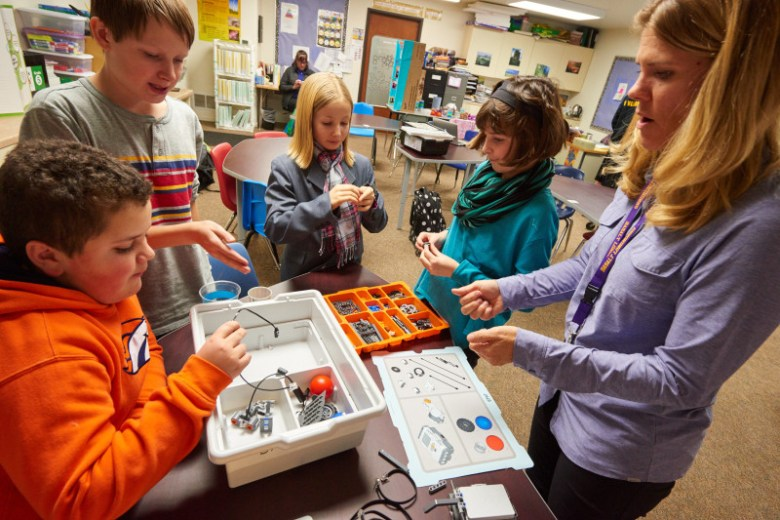 Members of the Longhorn Bots discuss strategy and tinker as teacher Kerry Williams looks on.