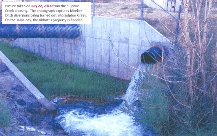 A photo from the Resource Engineering report documenting waste on the Meeker Ditch in 2014. Water from the ditch is being turned out into Sulphur Creek, while the main flow in the ditch continues through the pipe above the outfall.