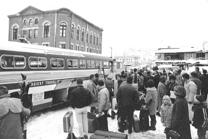 A crowd of people waiting next to a bus in Aspen in 1965. The bus says, Glenwood-Aspen Stage. By the mid-sixties, Aspen was gaining in popularity among visiting skiers.