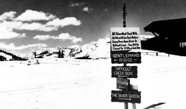 A sign at the top of Aspen Mountain in 1950 shows the Silver Queen trail starting atop Aspen Mountain. The trail went down Buckhorn, across Midway Road, down International, and down what is today's steep Silver Queen run on lower Aspen Mountain The sign says 'All skiers must check with ski patrol at Sundeck before going down Annie Basin or Difficult Creek. They will be closed by 12:00 each day.' The first version of the Sundeck, known as the Octagon, is partially visible behind the sign.