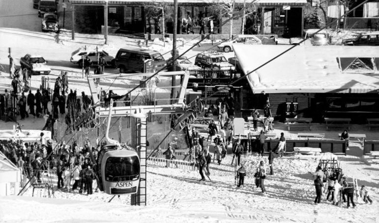The gondola at the bottom of Little Nell in mid-winter of 1987, showing a free-flowing lift line before corrals, and not a single skier wearing a helmet. To the right is the deck of the onetime Little Nell, bar, restaurant, and night club (down stairs—originally called 'Nell's Bottom' in the 1970s). Raucous crowds gathered on the deck on spring days. In the background note the free all-day on-street angle parking along Durant Street for the lucky early-bird skiers.