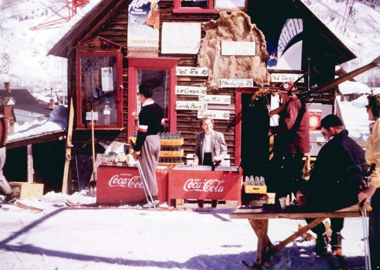 The Ski Inn, 1952. Ruth Whyte stands behind Coca Cola coolers. A Lift-1base tower is just behind the Inn on the left. Note the elk or bear hide nailed to the wall above Ruth and that an apple costs twice as much as a candy bar.