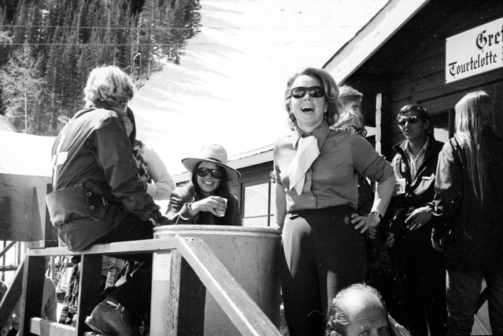 A group of people are caught in a moment outside of Gretl's 'Tourtelotte Restaurant' on the closing day of Lift 1, April 10, 1971. Gretl, in stylish Bavarian attire, smiles at the camera. Ski patrolman 'Kid' Cunningham is sitting on the railing. Patrolman Erik Peltonen is exiting the door with his face to the camera.