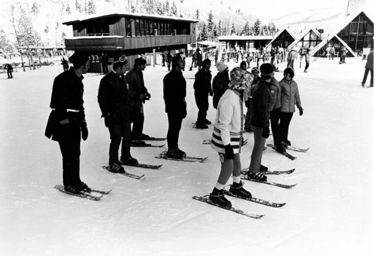 A Clif Tayler 'GLM' (Graduated Length Method) class standing ready in front of the A-framed Highlands base lodge in 1975. Behind to the left is the one-time administration building and ticket office. Clif Tayler's GLM method offered a five-day ski-week package, wherein he took rank beginners up through a series of longer skis during the week, to a point where they could parallel-ski and do a 'wedeln' (An Austrian, quick, side-to-side series of turns).