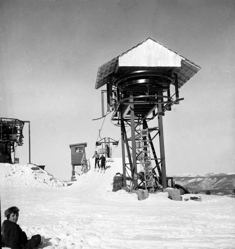 A pair of skiers getting off the top of old lift 3 on top of Aspen Mountain in 1954. The top bullwheel in the center stood where the Guest Service Center is today. The top of Lift 2 is to the left, and to the left of that, unseen, is the Aspen Mountain Patrol building.