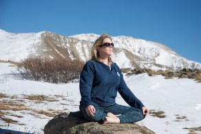 Judy sitting cross-legged in yoga pose on a rock in the snowy wilderness