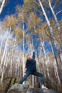 Judy in a standing yoga pose in a grove of aspen trees on a sunny day