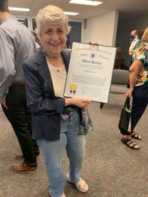 Eva Rajczyk holding up Senate Citation