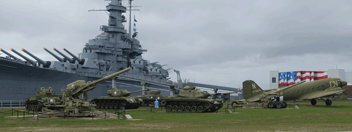 Tanks and other vehicles in front of the USS Alabama.