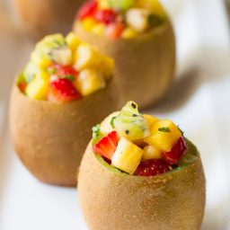Tropical Fruit Salad in Kiwi Cups on ASpicyPerspective.com #fruitsalad #kiwi