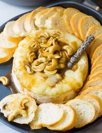 Dying over this Baked Brie with Cashews and Bourbon Brown Sugar Glaze Recipe on ASpicyPerspective.com. #holidays #christmas
