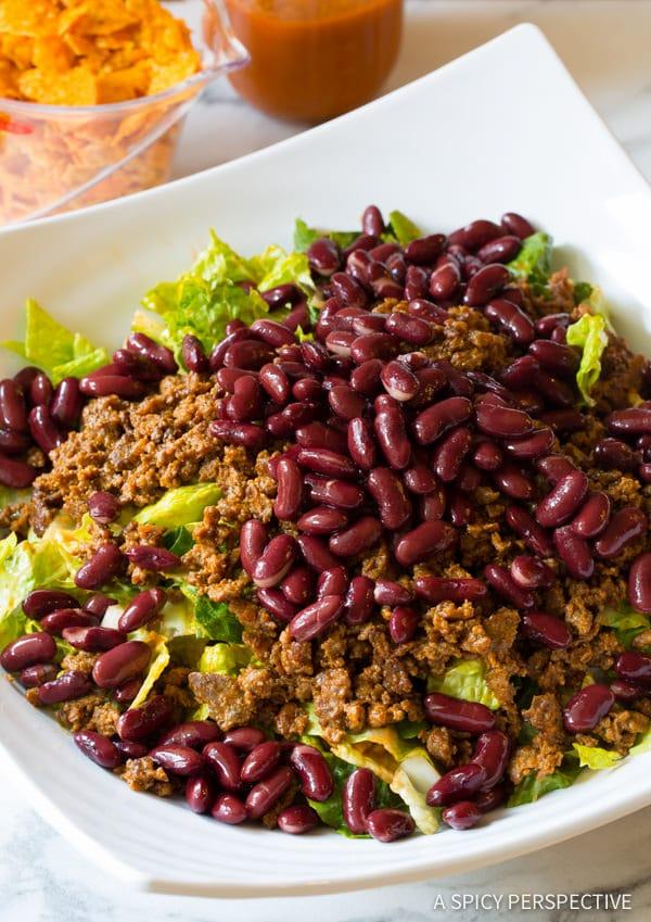 Adding Taco Meat and Kidney Beans #ASpicyPerspective #TacoSalad #TacoSaladRecipe #DoritoTacoSalad #DoritoTacoSaladRecipe #Doritos #TacoSaladDressing #HowtoMakeTacoSalad #TacoSaladIngredients #Salad