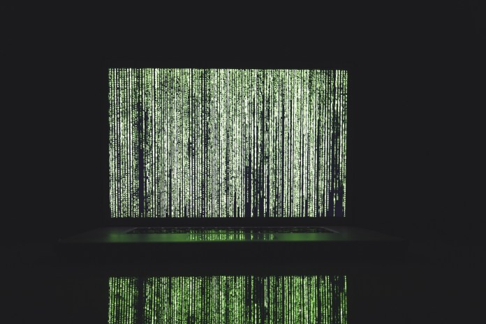A laptop displaying The Matrix code | Aspioneer