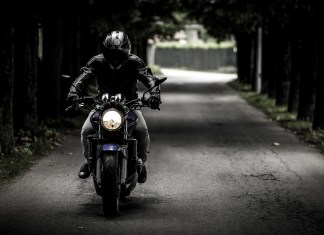 A motorcyclist riding down the road | Aspioneer
