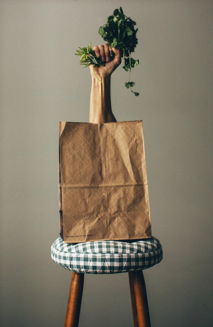 A hand clutching a vegetable popping out of paper bag