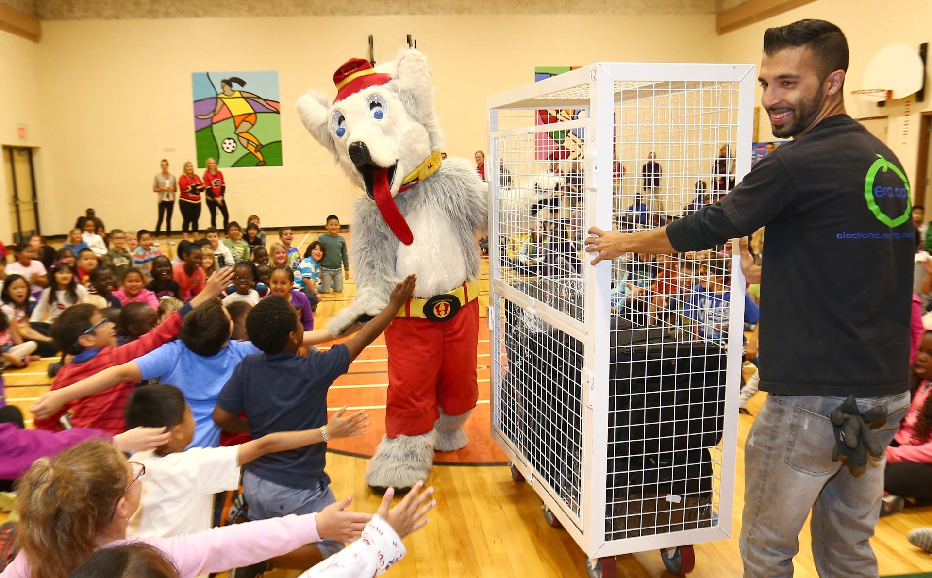 Students at St. Peter School give out a cheer as they had a special visit by The Calgary Flames' mascot, Harvey the Hound thanks to The Electronic Recycling Association (ERA) who donated 20 refurbished laptops which where presented to deserving students in Calgary on Wednesday June 17, 2015.