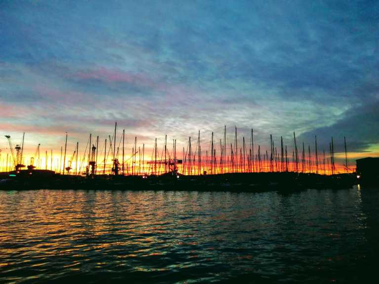 ship masts against a sunset