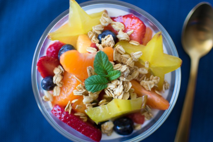 Overhead closeup picture of Meal Prep Fruit Salad in a bowl with yogurt and granola