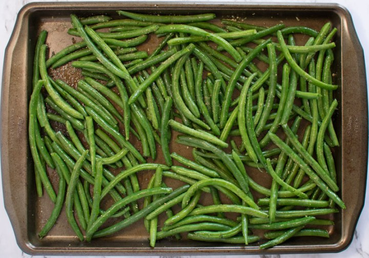 Uncooked, seasoned beans on a baking sheet