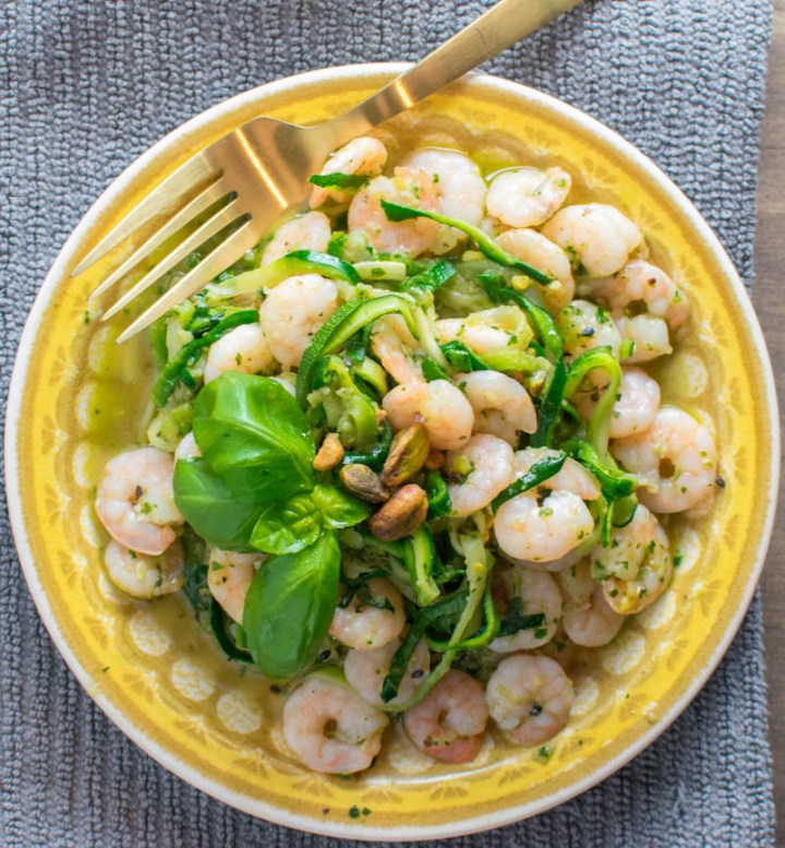 Overhead picture of shrimp pesto zoodles on a yellow plate with gold fork