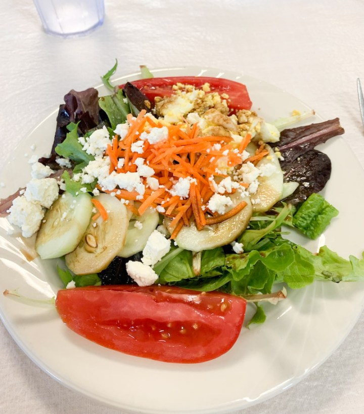Salad from salad bar made with greens, cucumber, tomatoes, carrots, hard boiled egg, feta cheese and balsamic vinegar.