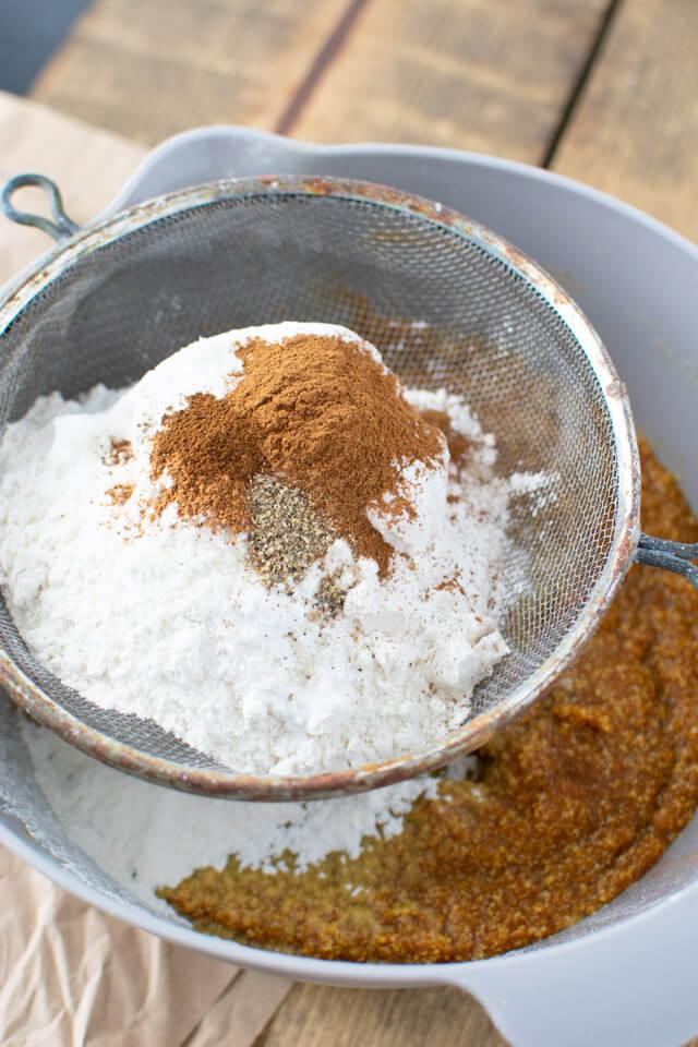 Sifting dry ingredients into pumpkin batter ingredients
