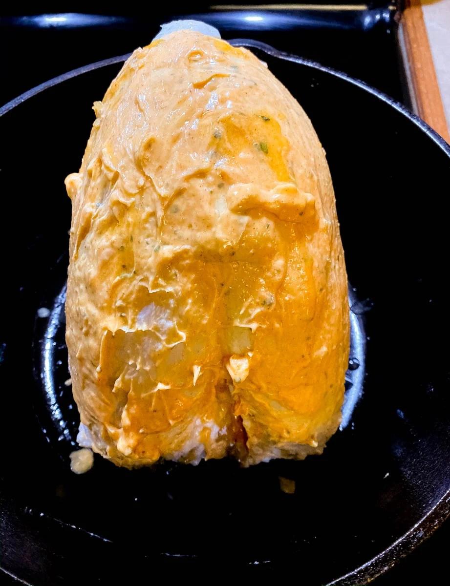Cajun butter rubbed turkey breast in a black cast iron Dutch oven.