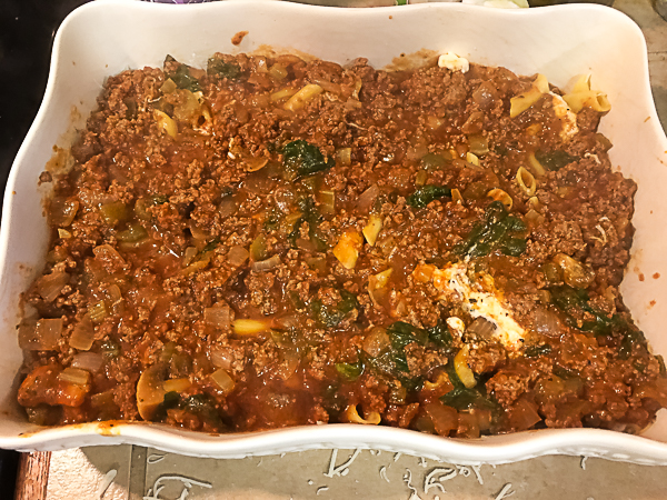 A layer of chunky tomato and ground beef sauce for Gluten Free Baked Ziti With Spinach and Mushrooms. | https://asprinklingofcayenne.com