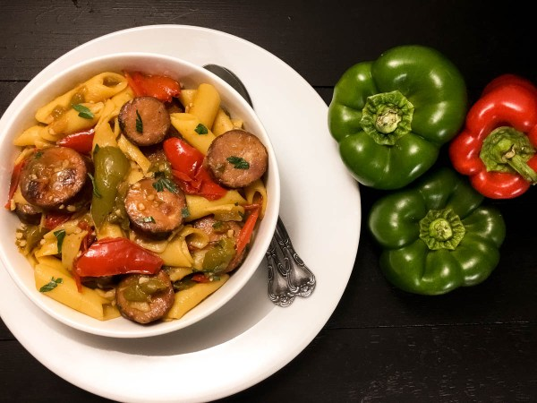 A bowl of yum-delicious Gluten Free Cajun Sausage and Peppers Pasta from A Sprinkling of Cayenne. | https://asprinklingofcayenne.com