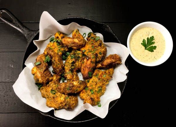 A Cast Iron Skillet Full of Gluten Free Creole Mustard Chicken Wings and Tenders. | https://asprinklingofcayenne.com