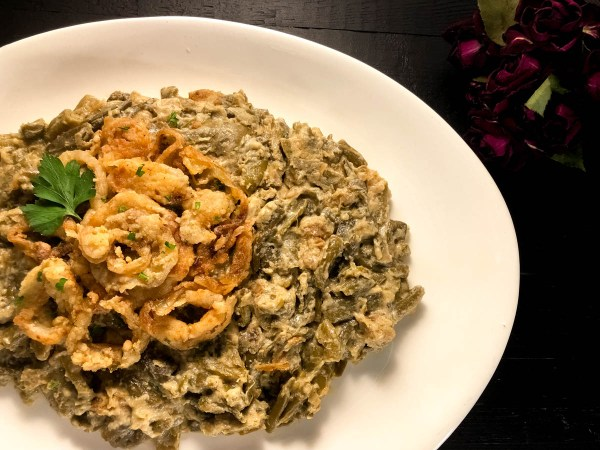A plate of yum-delicious Gluten Free Cajun Smothered Green Bean Casserole from A Sprinkling of Cayenne. | https://asprinklingofcayenne.com