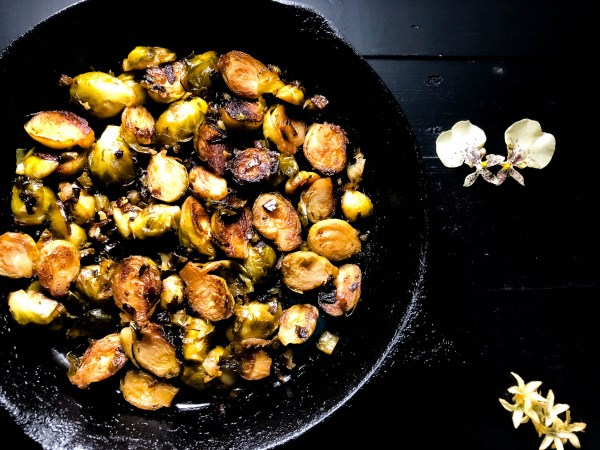 Flowers and a skillet and Cajun Pan Fried Brussels Sprouts. https://asprinklingofcayenne.com