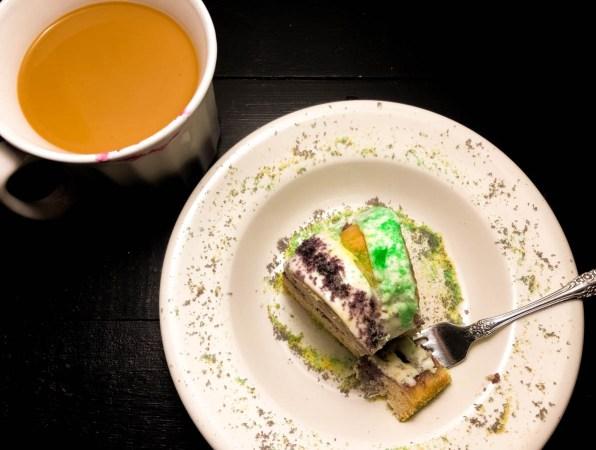 A slice of colored sugar light, icing heavy variation of Blueberry Cream Cheese Gluten Free King Cake Bundt Cake. | https://asprinklingofcayeenn.com