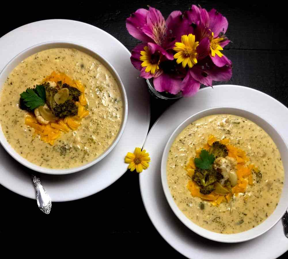 Gluten Free Roasted Broccoli and Cauliflower Cheese Soup in two white bowls with yellow and magenta flowers.