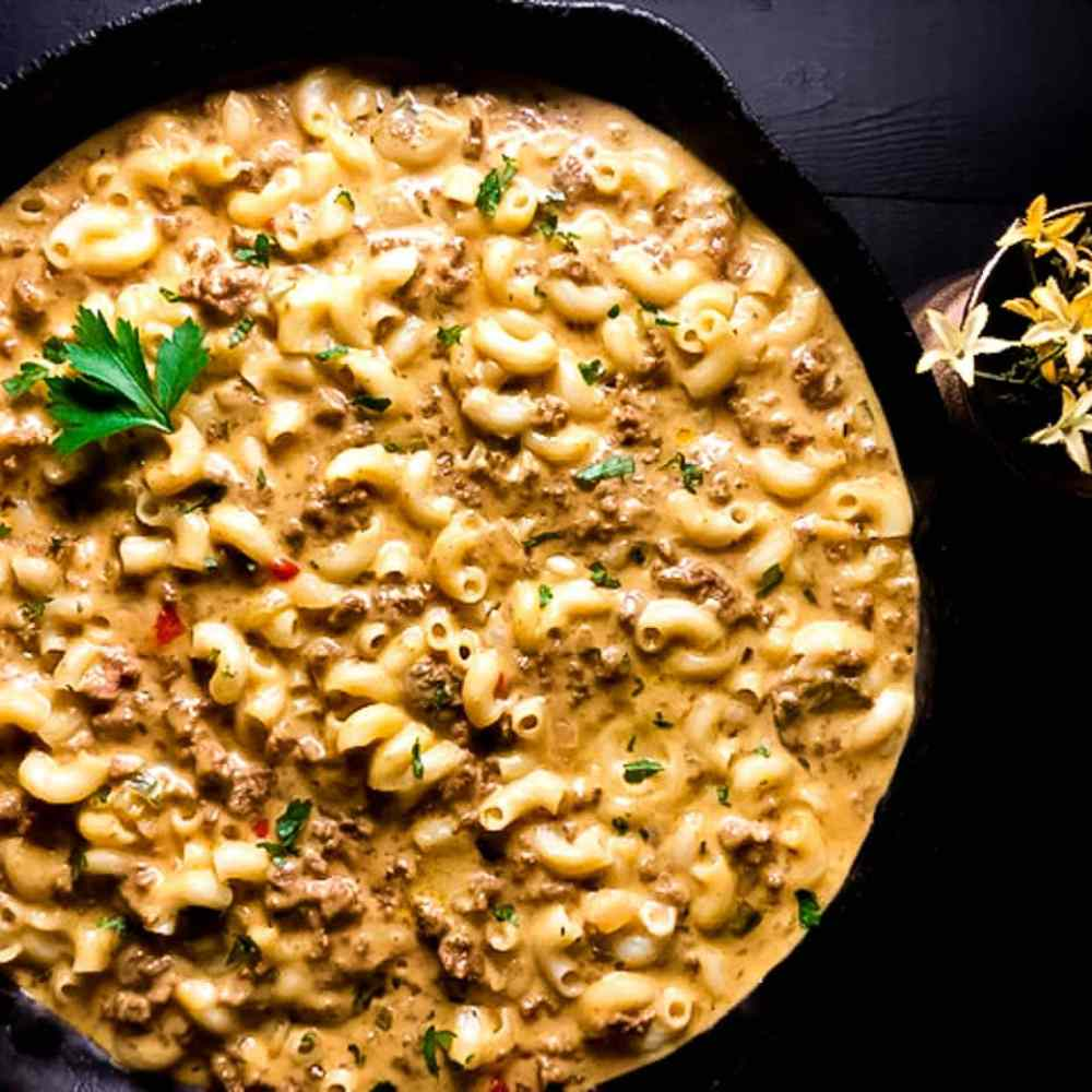 Best Ever Gluten Free Cheeseburger Macaroni Skillet against a black background with yellow flowers. | https://asprinklingofcayenne.com