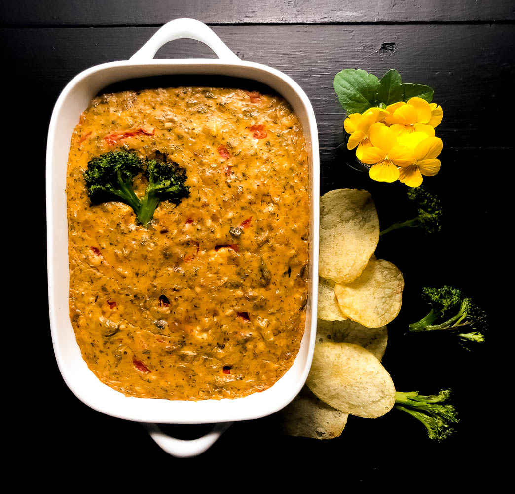 A small white casserole dish filled with Grain Free Cheesy Roasted Broccoli Dip. | https://asprinklingofcayenne.com