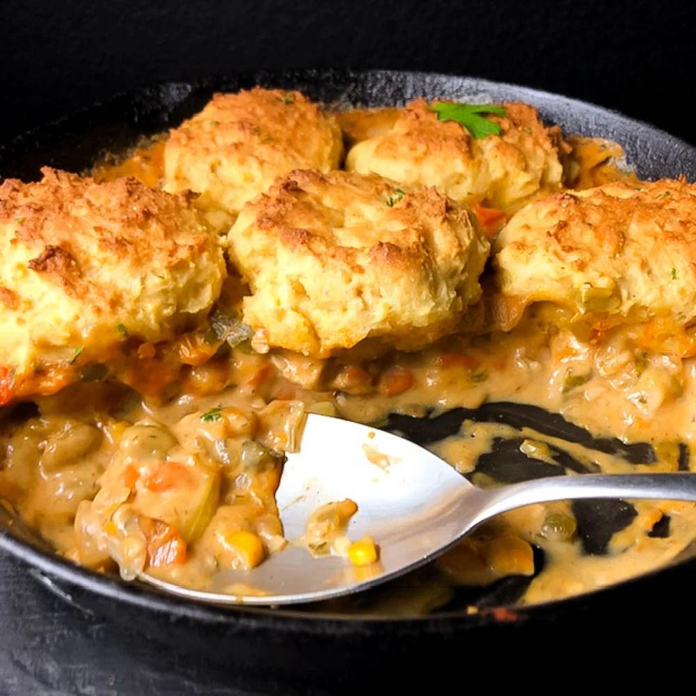 A side view of Cornbread Biscuit Topped Gluten Free Chicken Pot Pie in a cast iron skillet. | https://asprinklingofcayenne.com