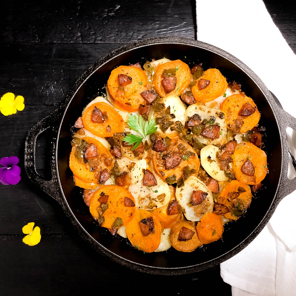A round skillet holding south Louisiana sassified skillet potatoes with sausage with flowers and a white napkin.