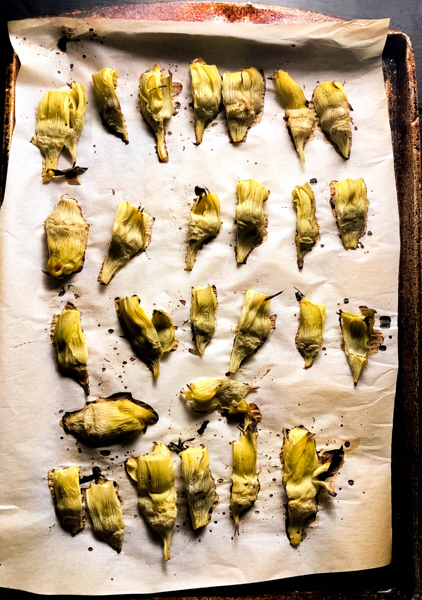 Roasted canned artichoke hearts on a parchment paper-lined baking sheet.
