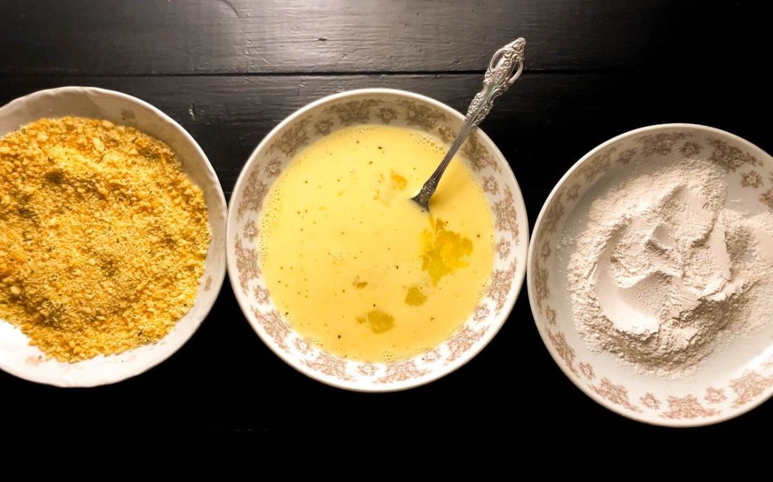 Three shallow bowls with cassava flour, egg wash, and gluten free bread crumbs against a black background.