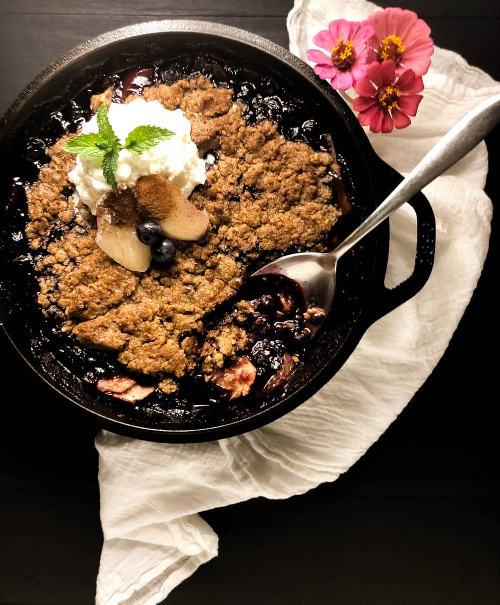 A black cast iron skillet filled with grain free blueberry pear crisp with a white napkin against a black background.