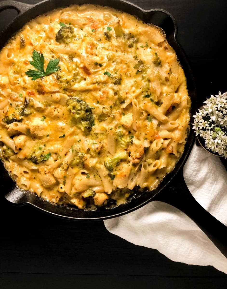 A black iron skillet filled with freshly baked Best Ever Gluten Free Cheesy Chicken Broccoli Pasta against a black background.
