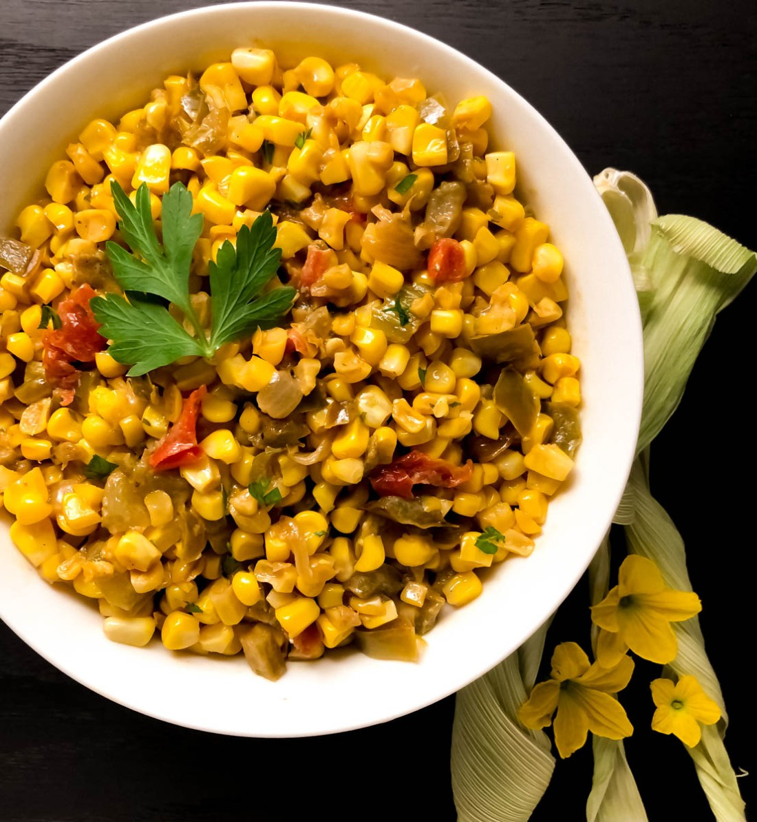 A round white bowl filled with spicy skillet corn maque choux.