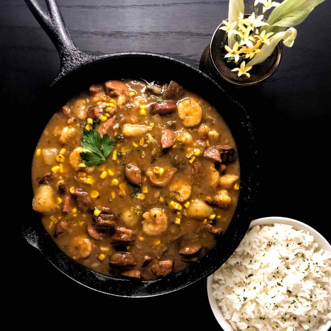 A black cast iron skillet filled with Gluten Free Cajun Shrimp, Corn Maque Choux and Sausage Stew