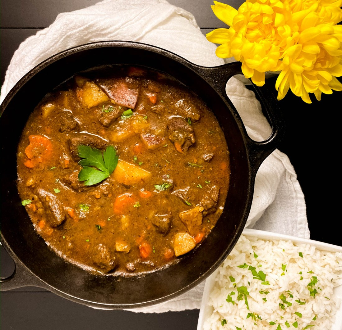 A cast iron skillet filled with freshly cooked grain or gluten free Cajun beef stew.