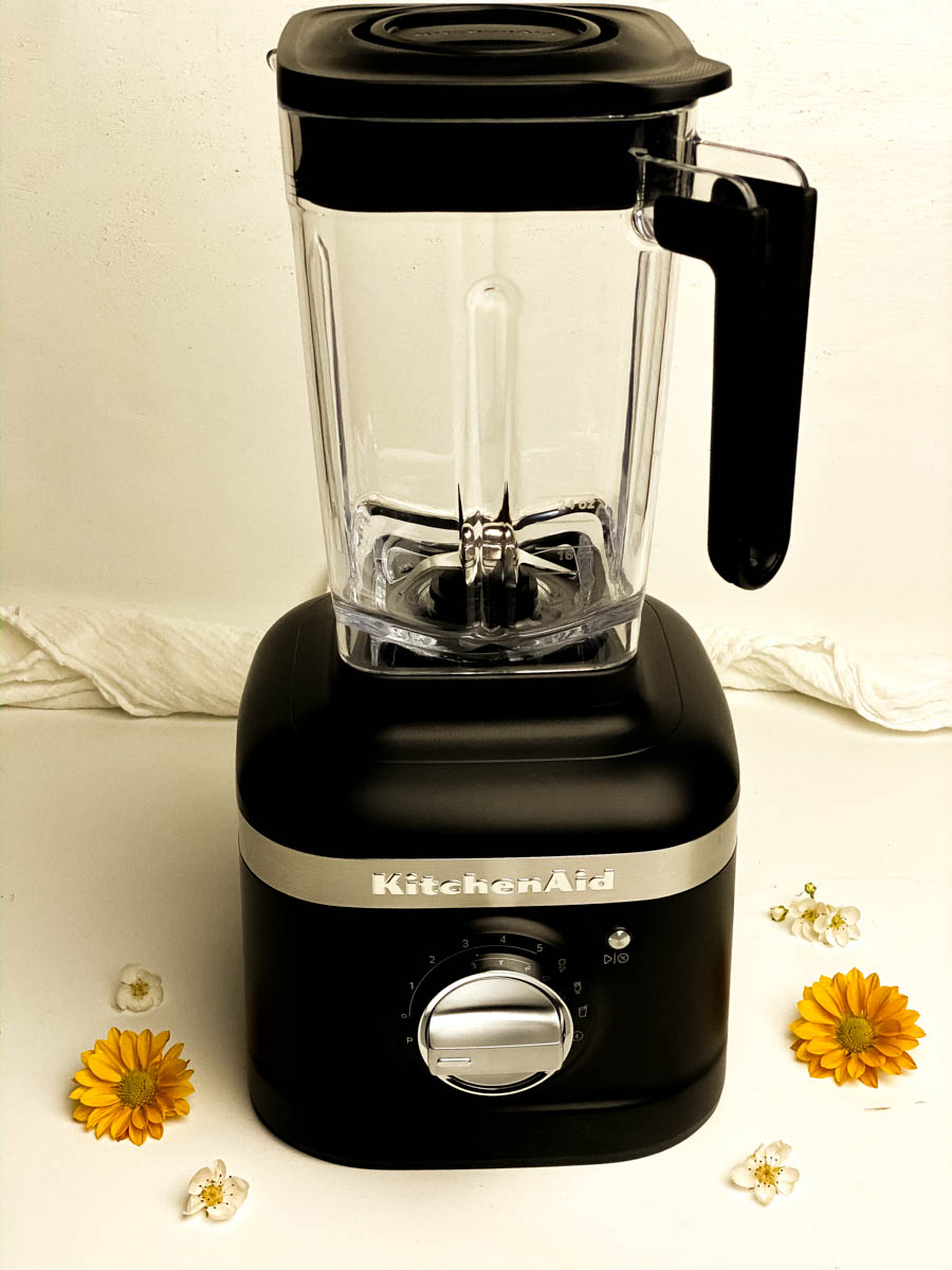 Black K400 Kitchenaid blender against a white background with flowers.