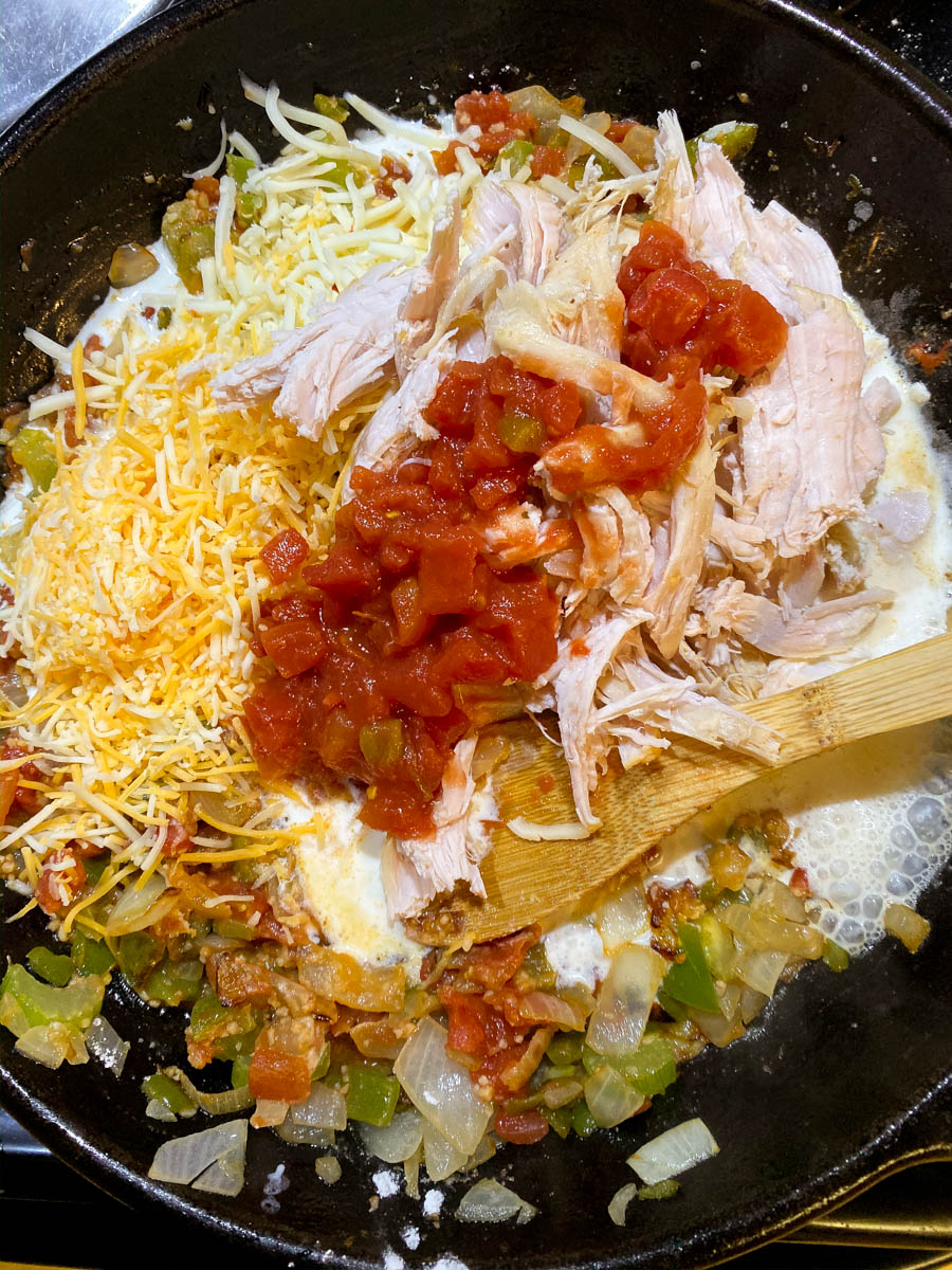 Veggies, cheese and turkey cooking down in a skillet