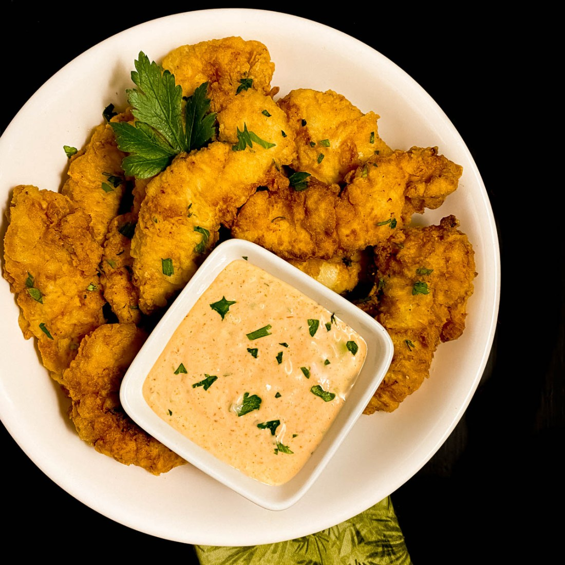 A round white bowl with Cajun fried chicken tenders and remoulade sauce.