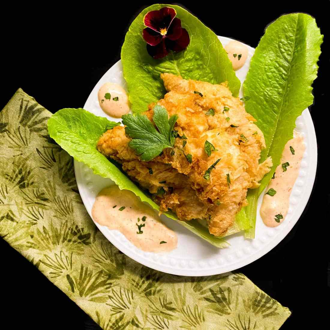 Grain & Gluten Free Fried Chicken Tenders with Remoulade Sauce on a white plate against a black background.